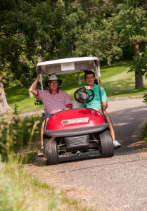 two men riding in a golf cart